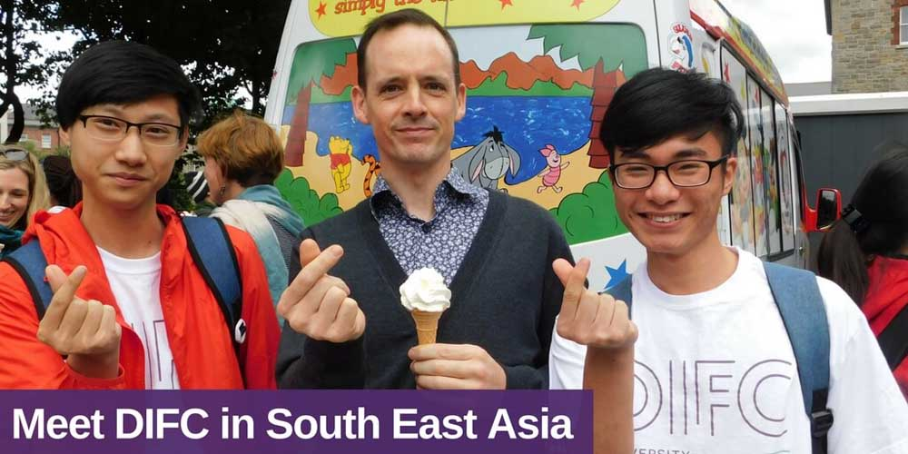 Three males (two students and one DIFC representative) infront of an ice cream van, one male holding an ice cream