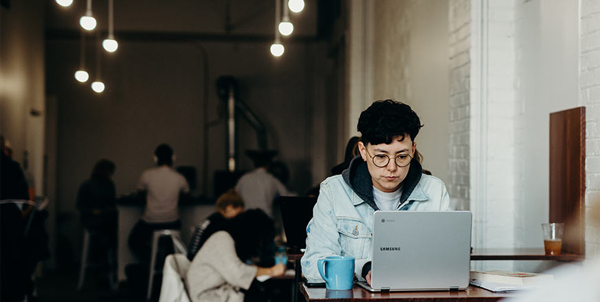 Malaysian male student sitting at a table, typing on a laptop with a cup beside him