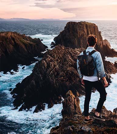 Man standing on rocks looking at the ocean