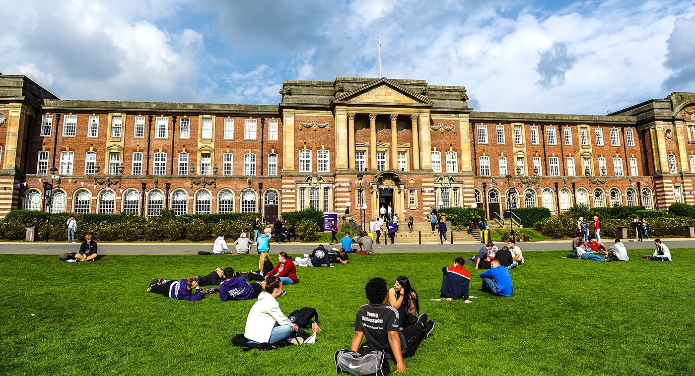 Old building with students sitting on the grass outside