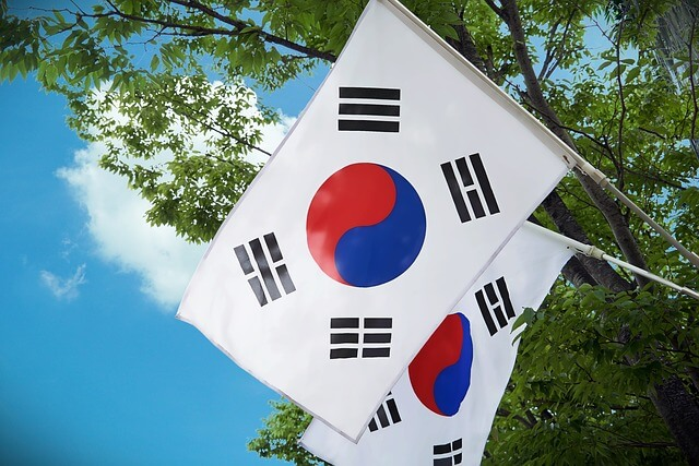 Two South Korea flags hanging in front of trees