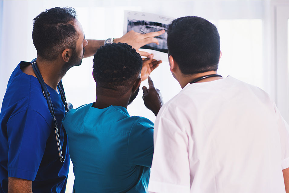 3 DIFC student dentists looking at an x-ray